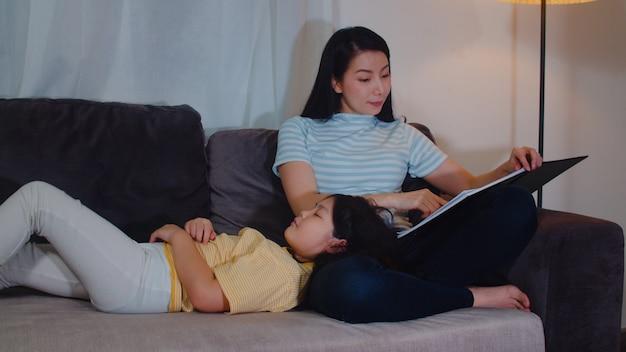 Jonge aziatische moeder thuis gelezen sprookjes aan haar dochter. de gelukkige chinese familie ontspant met tienermeisje dat terwijl het luisteren aan verhalen liggend op bed in slaapkamer bij modern huis bij nacht slaapt.