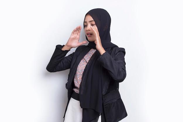 Jonge aziatische mooie moslimvrouw schreeuwen en schreeuwen aankondigen geïsoleerd op een witte achtergrond
