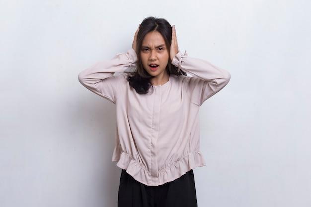 Jonge aziatische mooie vrouw die beide oren bedekt met handen geïsoleerd op een witte achtergrond