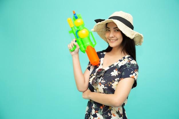 Jonge aziatische mooie vrouw die plastic waterkanon houdt dat op groene achtergrond, songkran-festival in thailand wordt geïsoleerd