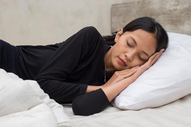 Jonge aziatische mooie vrouw slapen in slaapkamer
