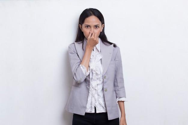 Jonge aziatische mooie zakenvrouw die haar neus vasthoudt vanwege iets dat slecht ruikt