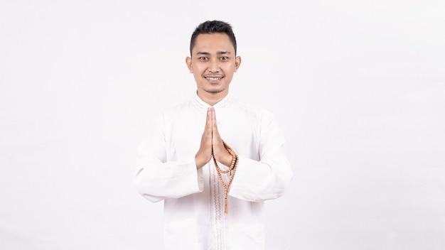 Jonge aziatische moslim man met groet en verwelkomend gebaar in ramadhan