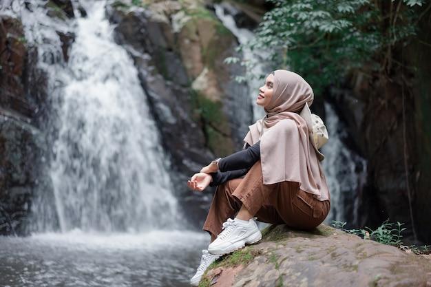 Jonge aziatische moslim toeristenvrouw die bruine hijab draagt, zittend op de rots voor waterval.