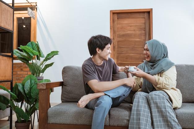 Jonge aziatische moslima-koppels maken een grapje terwijl ze genieten van koffie in de woonkamer