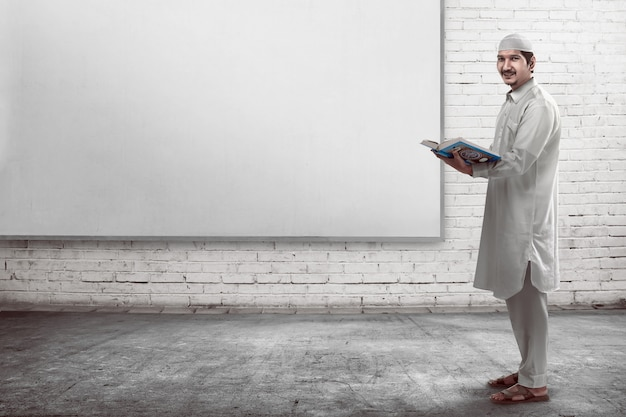 Jonge aziatische moslimmensen die koran lezen