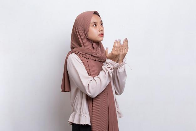 Jonge aziatische moslimvrouw bidden geïsoleerd op witte achtergrond
