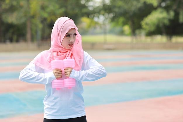 Jonge aziatische moslimvrouw die buiten staat en halters optilt om te oefenen met een groene boomachtergrond