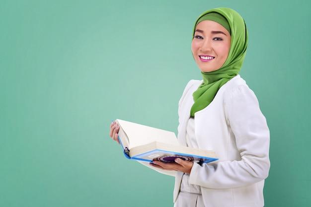 Jonge aziatische moslimvrouw die de koran houdt