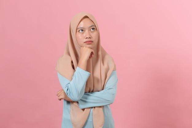 Jonge aziatische moslimvrouw die een exemplaarruimte bekijkt of een idee denkt; geïsoleerd op roze achtergrond