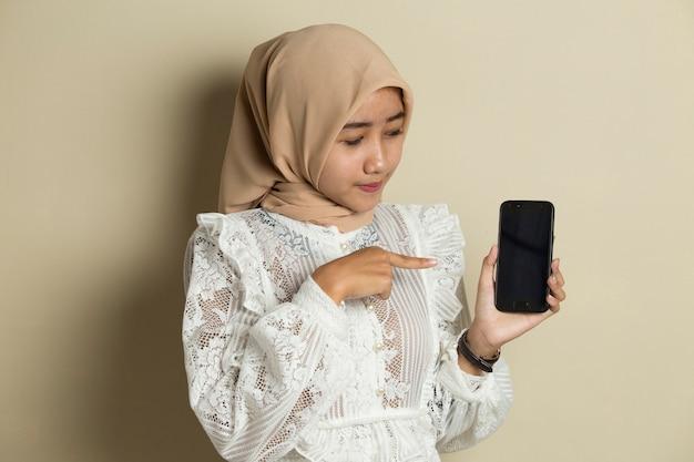 Jonge aziatische moslimvrouw die hijab draagt die leeg scherm mobiele telefoon toont