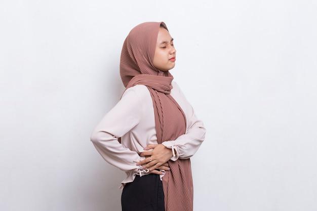 Jonge aziatische moslimvrouw die lijdt aan lage rugpijn en lumbale pijn in de taille