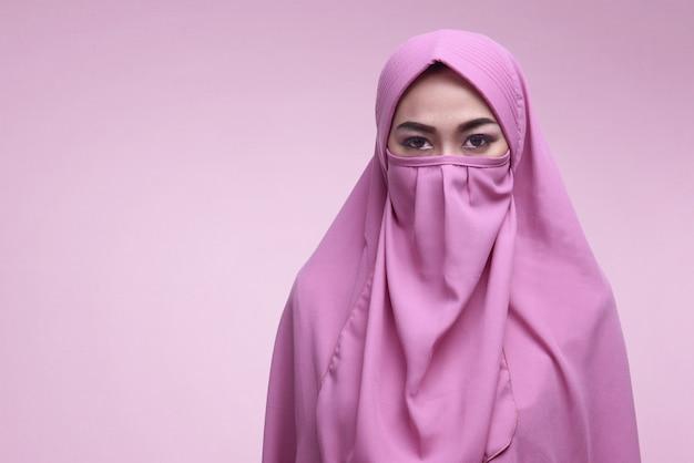 Jonge aziatische moslimvrouw die niqab draagt