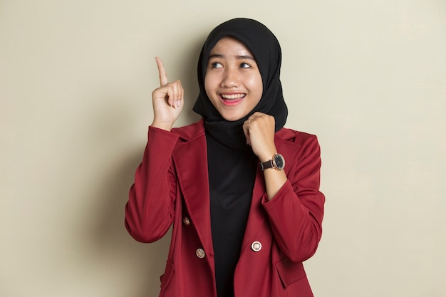Jonge aziatische moslimvrouw heeft een goed idee. gelukkig lachend meisje geïsoleerd op een grijze achtergrond.