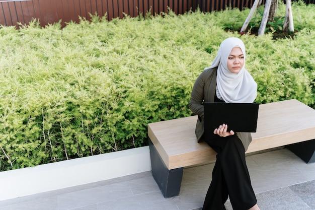 Jonge aziatische moslimvrouw in groene pak en werken op een computer in het park.