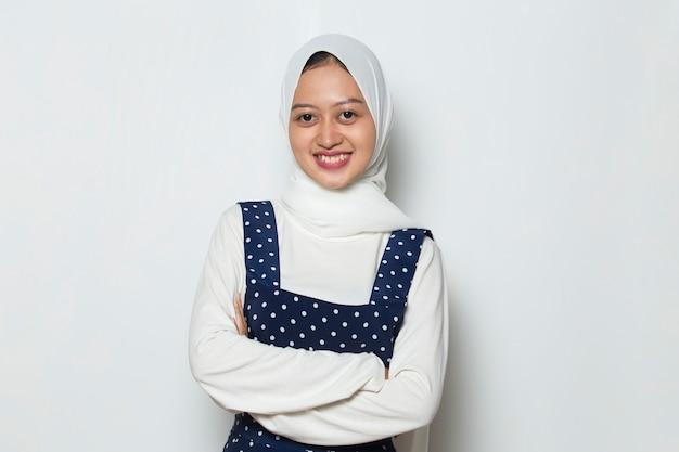 Jonge aziatische moslimvrouw in hoofddoekglimlach met gekruiste armen