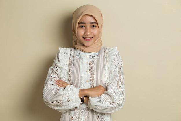 Jonge aziatische moslimvrouw in hoofdsjaalglimlach met gekruiste wapens