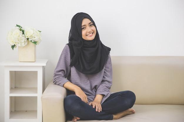 Jonge aziatische moslimvrouw in hoofdsjaalglimlachen