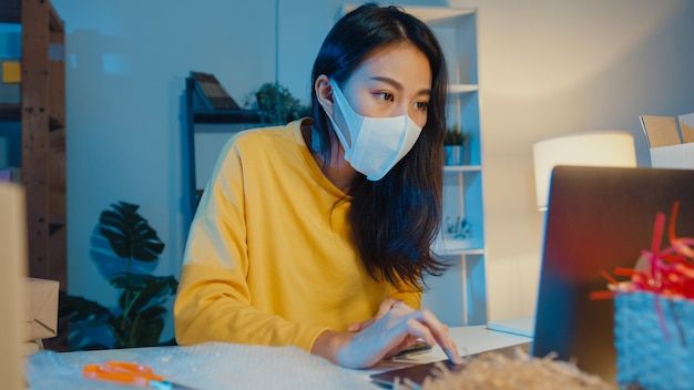 Jonge aziatische onderneemster die gezichtsmasker draagt die inkooporder controleert en de chat van de cliëntinbox op laptop beantwoordt