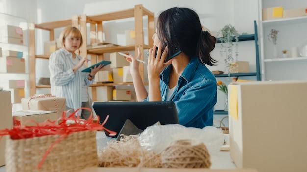 Jonge aziatische onderneemster die gezichtsmasker draagt die mobiele telefoon met behulp van die inkooporder ontvangt en product op voorraadwerk thuisbureau controleert