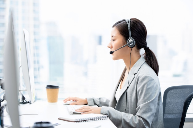 Jonge aziatische onderneemster die hoofdtelefoons dragen die in het bureau van de call centrestad werken als telemarketingexploitant