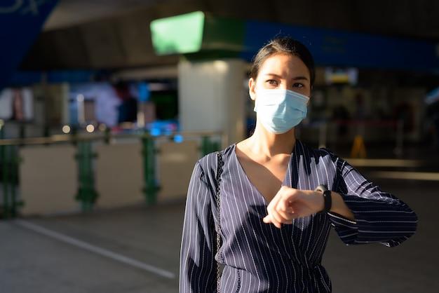 Jonge aziatische onderneemster die met masker de tijd controleert tijdens het weglopen van het treinstation