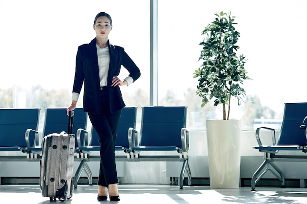 Jonge aziatische onderneemster in luchthaven met karretjezak, die op vertrek wacht
