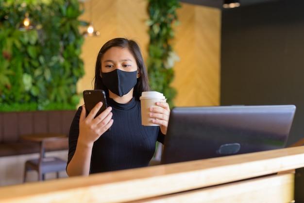 Jonge aziatische onderneemster met masker die telefoon gebruiken en met afstand binnen de coffeeshop zitten