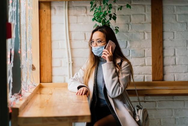 Jonge aziatische onderneemster met masker die telefoon gebruiken en met afstand buiten de coffeeshop zitten