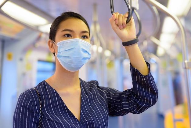Jonge aziatische onderneemster met masker voor bescherming tegen uitbraak van het coronavirus die de trein berijdt