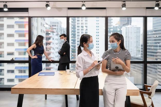 Jonge aziatische onderneemstercollega die gezichtsmasker draagt en in nieuw normaal bureau spreekt, kaukasisch uitvoerend bespreken