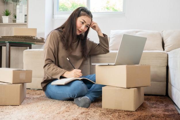 Jonge aziatische ondernemer die stress en angst voelt als gevolg van verminderde verkoop na het controleren van bestellingen