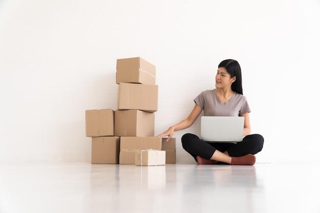 Jonge aziatische ondernemer die stress en angst voelt als gevolg van verminderde verkopen na het controleren van bestellingen van klanten met een laptop.