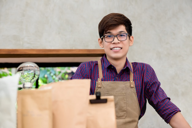 Jonge aziatische ondernemer die zich bij teller in koffiewinkel bevindt
