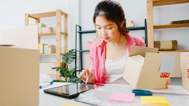 Jonge aziatische ondernemer zakenvrouw controleren product inkooporder op voorraad en opslaan op tabletcomputer werk thuis kantoor. kleine ondernemer, online marktlevering, freelance lifestyleconcept.
