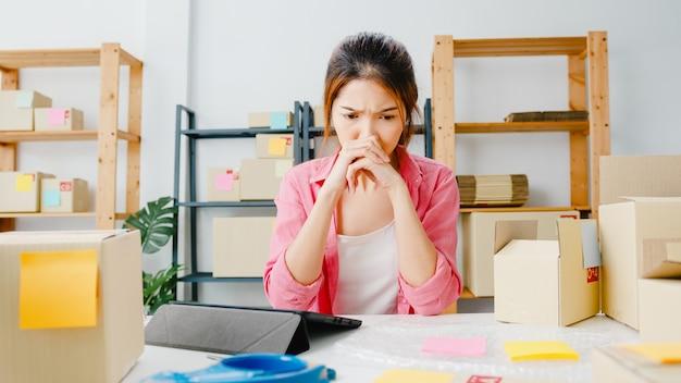 Jonge aziatische ondernemer zakenvrouw controleren product inkooporder op voorraad, met behulp van tablet hard werken overbelasting thuis kantoor. kleine ondernemer, online marktlevering, freelance lifestyleconcept.