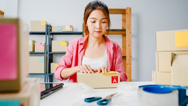 Jonge aziatische ondernemer zakenvrouw verpakking product in kartonnen doos leveren aan klant, thuis kantoor werken. eigenaar van een klein bedrijf, start online marktbezorging, freelance lifestyleconcept.