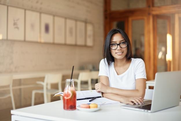 Jonge aziatische ondernemersstudent die aan laptop in bibliotheek of open ruimtecafé werkt die camera het glimlachen bekijkt.