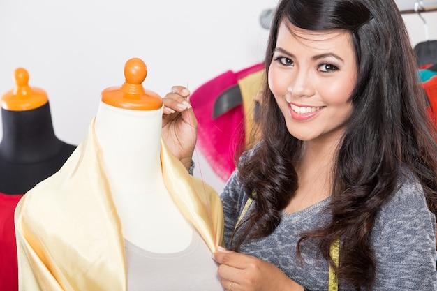 Jonge aziatische ontwerper die een stof op een ledenpop naait, het glimlachen