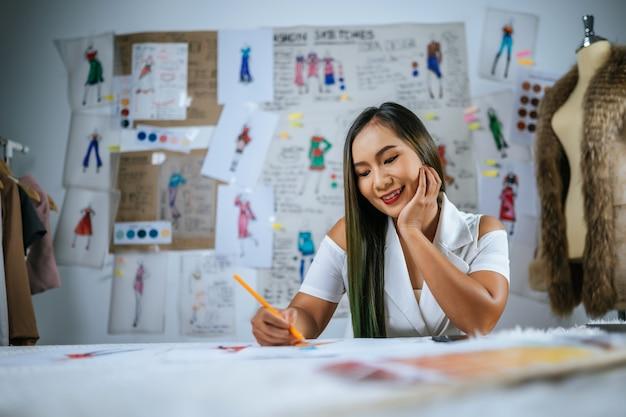Jonge aziatische ontwerper vrouwelijke tekening mode schets in werkplaats. mooie kleren schets foto aan boord achter haar