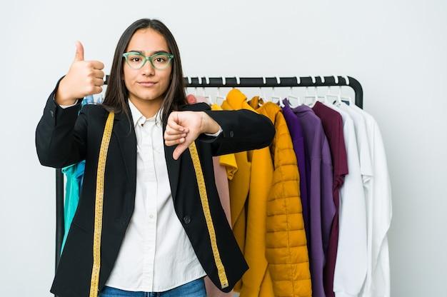 Jonge aziatische ontwerpervrouw die op witte muur wordt geïsoleerd die duimen omhoog en duimen omlaag tonen, moeilijk kiest concept