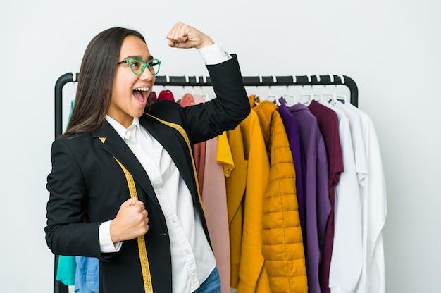 Jonge aziatische ontwerpervrouw die op witte muur wordt geïsoleerd die vuist opheft na een overwinning, winnaarconcept.