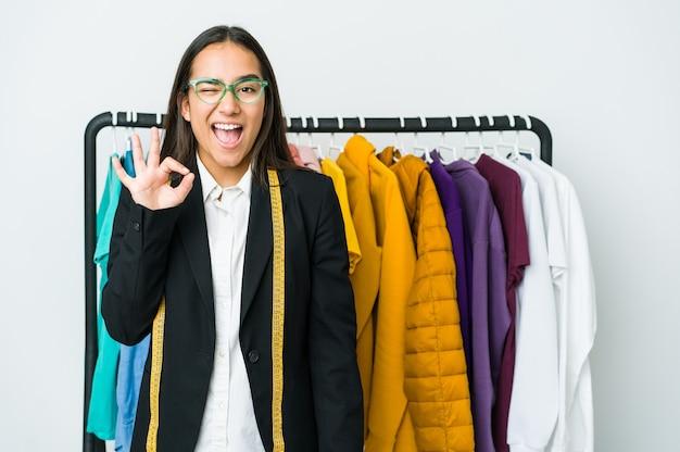 Jonge aziatische ontwerpervrouw die op witte muur wordt geïsoleerd, knipoogt en houdt een goed gebaar met de hand