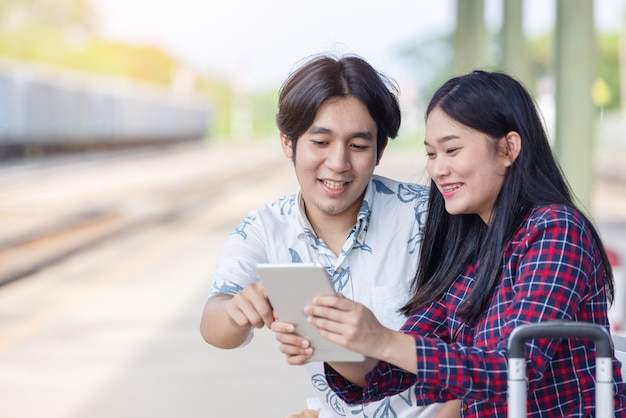 Jonge aziatische paar-backpacker die tablet gebruikt voor het vinden van een bestemmingsreis op het treinstation railway