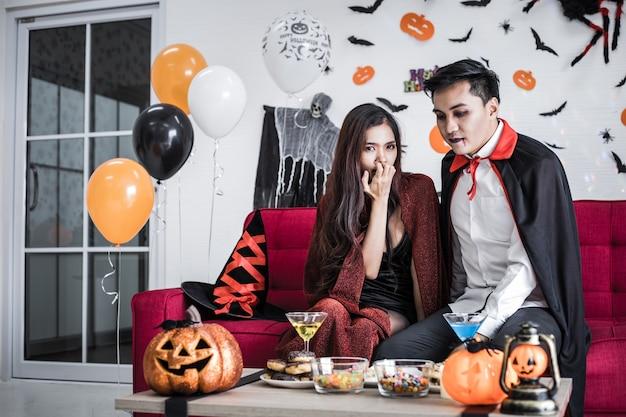 Jonge aziatische paar in kostuum heks en dracula met halloween feest vieren en samen wijn drinken in halloween festival op rode sofa in de kamer thuis.