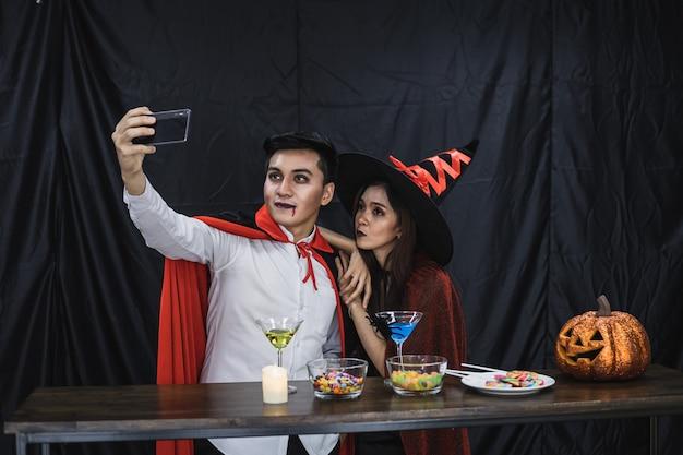 Jonge aziatische paar in kostuum heks en dracula met selfie door mobiel in vieren feest halloween festival. paar in kostuum vieren halloween-feest zwarte doek achtergrond. Premium Foto
