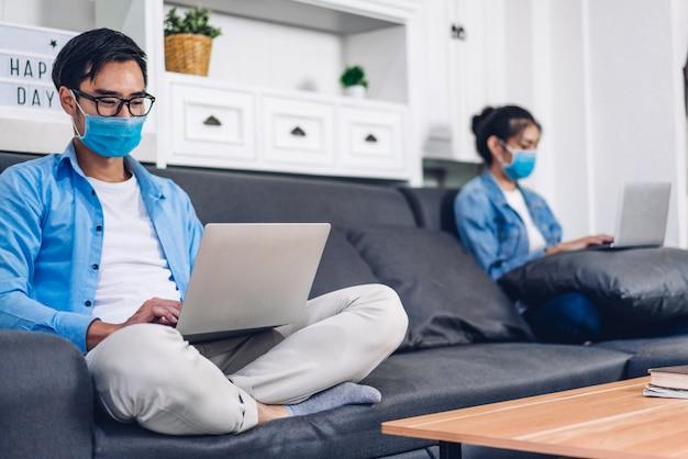 Jonge aziatische paar met behulp van laptopcomputer werken en videoconferentie vergadering online chat in quarantaine voor coronavirus dragen van beschermend masker met sociale afstand thuis. werk vanuit huis concept