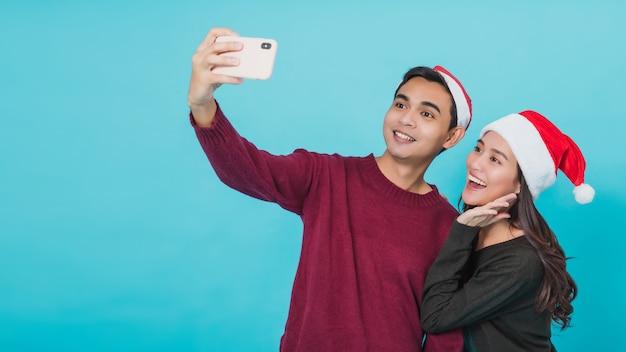 Jonge aziatische paar minnaar dragen kerstman hoed. hand met smartphone selfie samen geïsoleerd op blauwe achtergrond in studio opname. kerstviering van minnaar concept.