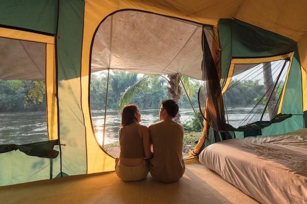 Jonge aziatische paar ontspannen in een tent op de camping in natuurpark 's avonds