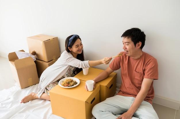 Jonge aziatische paar zitten op de vloer en eten geroosterde eendenei noodle op kartonnen verhuisdozen om te worden uitgepakt spullen in nieuw huis. hypotheekleningen en onroerend goed om een nieuw gezinsleven te beginnen.